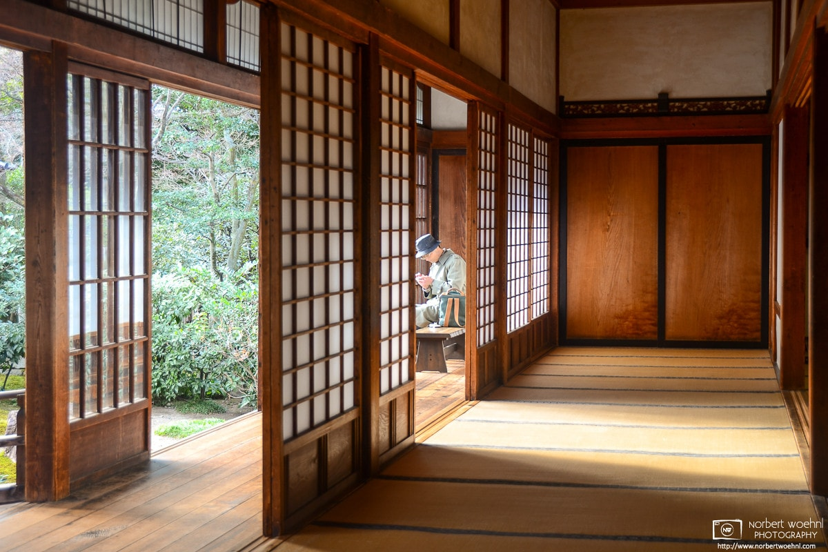 A visitor is seen reading between sliding doors outside a tatami room at Kenninji Temple in Kyoto, Japan.