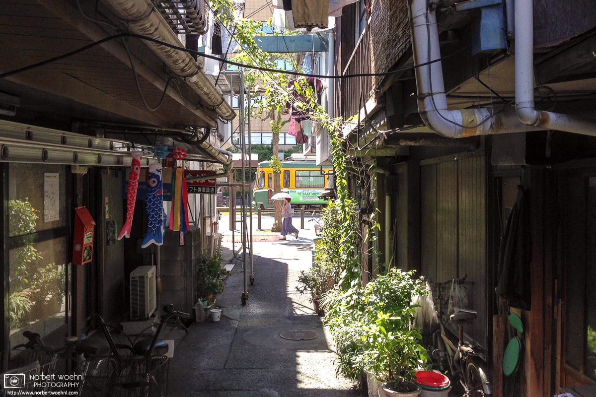 Through an alley of residential buildings in Kagoshima on the south western tip of the island of Kyushu in Japan, I captured this view of a city tram and a pedestrian carrying a parasol.