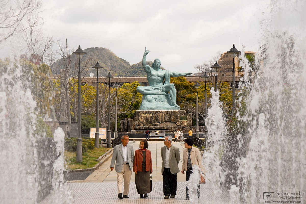 Framed by the water jets of a fountain at Nagasaki Peace Park in Japan, folks are seen having a pensive talk.