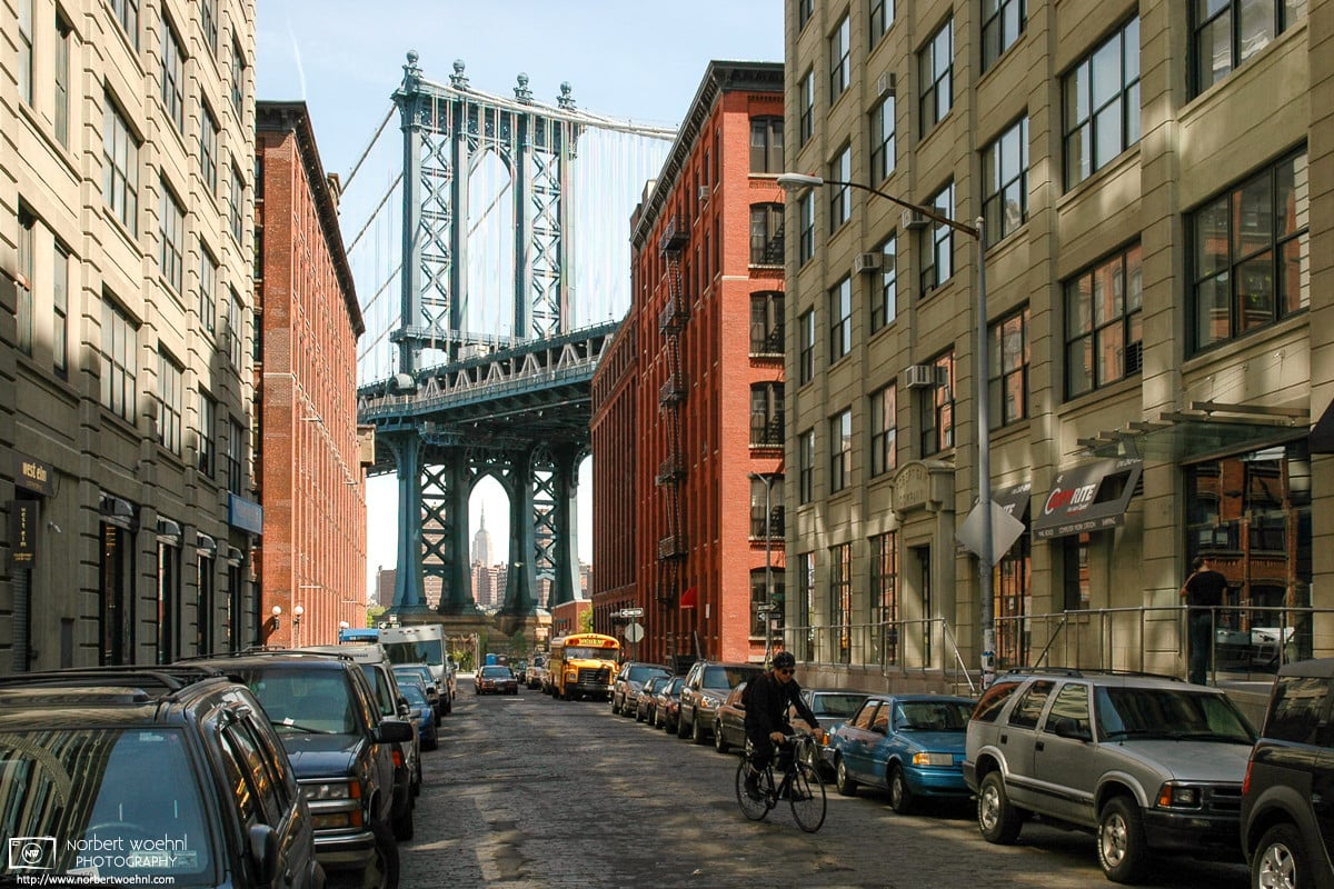 Taken in Brooklyn's DUMBO area, this photo from New York City looks north along Washington Street towards Manhattan Bridge and the distant silhouette of the Empire State Building in the background.