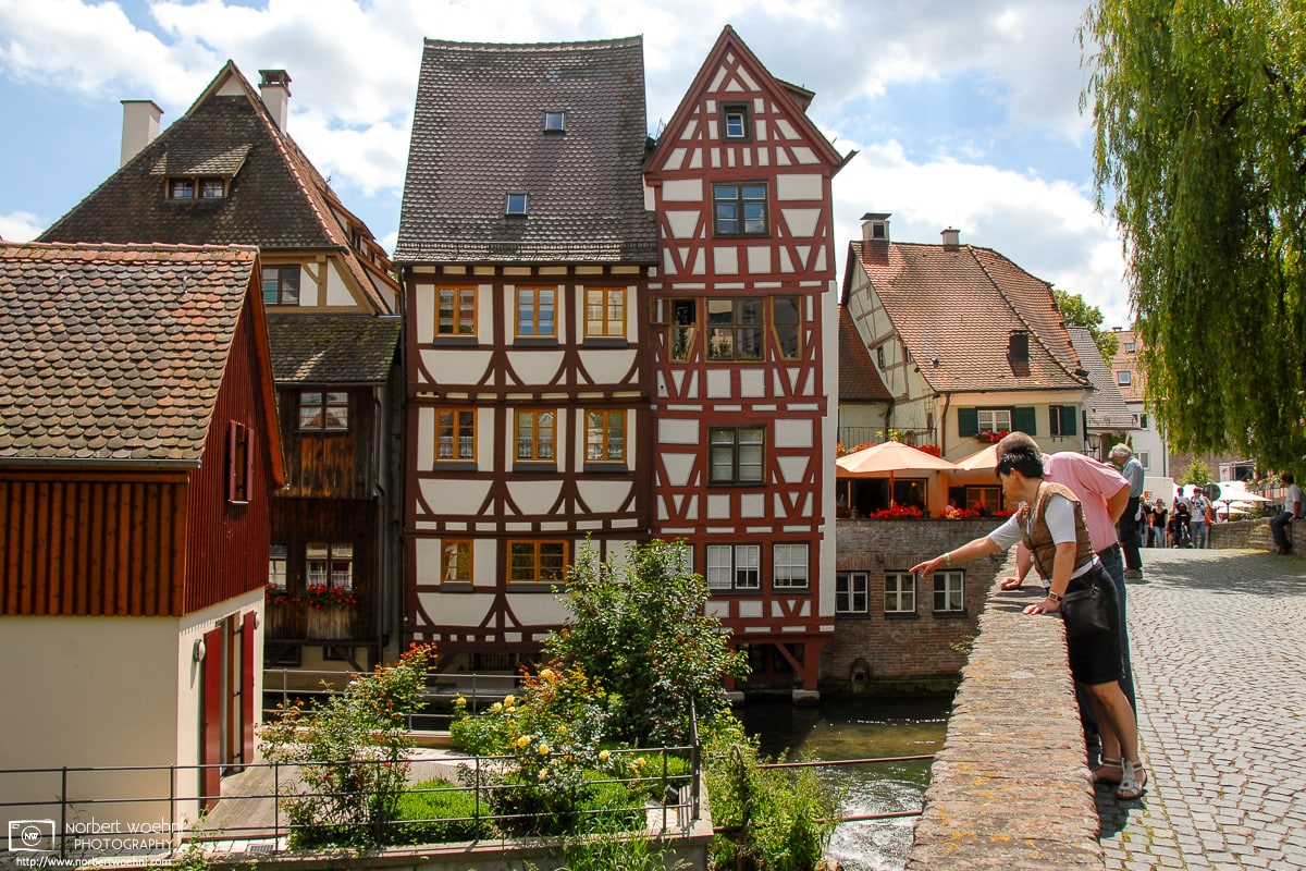 Visitors enjoying the view from Häuslesbruck in the historic Fisherman's Quarter (Fischerviertel) in Ulm, Germany.