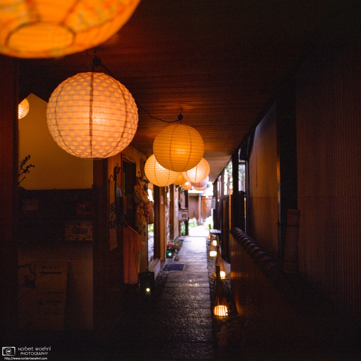 Lamps illuminate a corridor of a building with small shops in the Naramachi district of Nara, Japan.