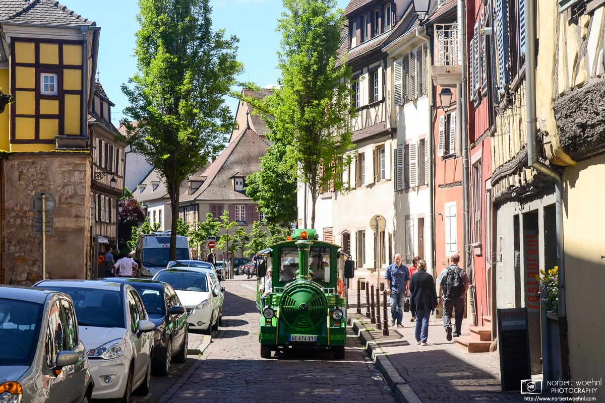 """A colorful """"tourist train"""" vehicle is seen navigating the old cobblestone streets of Colmar in Alsace, France."""
