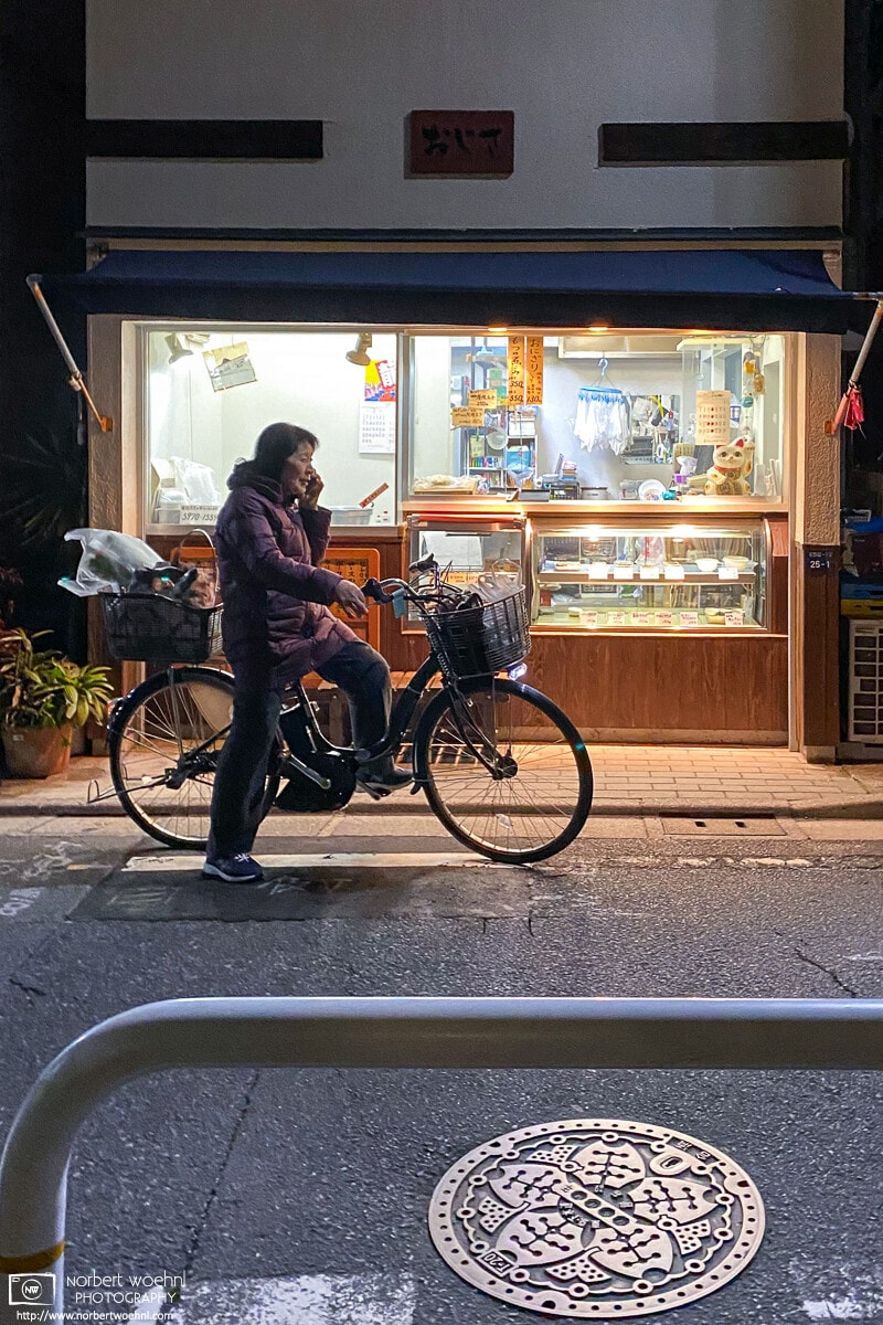 A woman is seen making a phone call in front of an old-style neighborhood shop in Itabashi-ku, Tokyo, Japan.